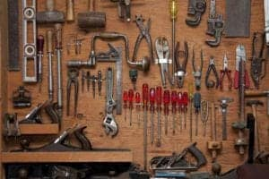 Assortment of do it yourself tools hanging in a wooden cupboard against a wall [shutterstock: 55814938, Daleen Loest]